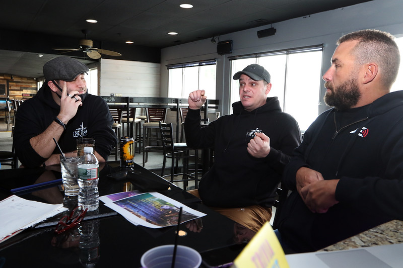 Seated from left, co-owners of The Boat, David Paquette of Pelham, N.H., and Devin Cordeiro of Dracut, AE Event Systems owner Dan Bouchard of Tyngsboro, who has been providing audio-visual for remote but  live band concerts. (SUN/Julia Malakie)