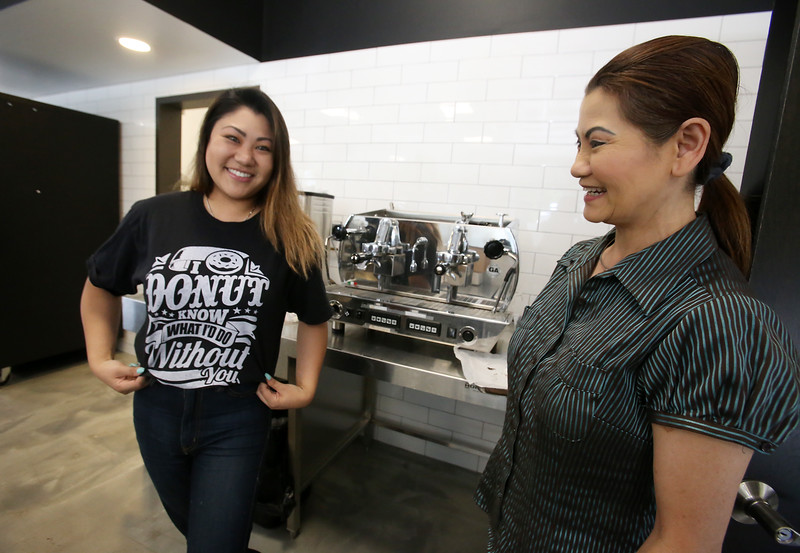 Top Donut co-owner Wendy Ley, right, and her daughter Cindy Ley, all of Dracut, at their new Dracut store, which Cindy will manage. (SUN/Julia Malakie)
