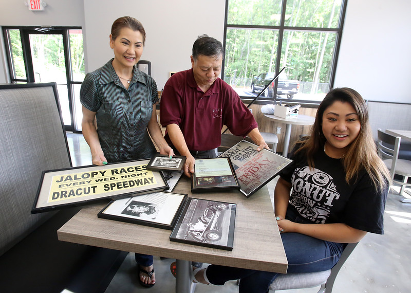 Top Donut owners Robin and wife Wendy Ley and their daughter Cindy Ley, all of Dracut, at their new Dracut store, which Cindy will manage. The memorabilia of the Dracut Speedway was given to them by Gerald Wooldridge from his collection. (SUN/Julia Malakie)