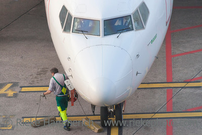 Düsseldorf, Germany - September 25, 2011: High angle view of Germania airplane cockpit  and ground technician on International Airport in Düsseldorf, Germany. The ground technician removes chocks from the front tires.