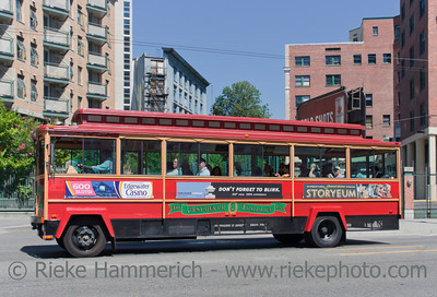 Vancouver, British Columbia, Canada – August 6, 2005: Tour Trolley Bus driving on East Pender Street in front of Apartment Buildings in Vancouver, Canada. Tourists enjoy a Vancouver Sightseeing Tour in a San Francisco-style Trolley.