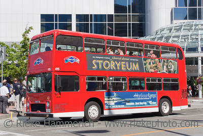 Vancouver, British Columbia, Canada – August 6, 2005: Red Double-Decker Bus standing on Bus Stop in Vancouver, Canada. Tourists enjoy a Vancouver Sightseeing Tour. In the Background the Pan Pacific Hotel near Canada Place with guests.