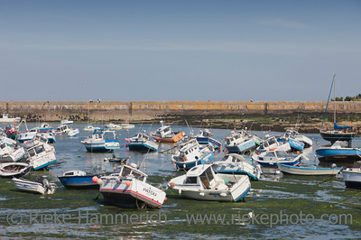 Barfleur, France - July 3, 2011: Fishing and recreational boats at low tide in the harbor of Barfleur, France. Barfleur is a picturesque fishing village on the peninsula Cotentin in Basse Normandy. In the middle ages Barfleur was one of the chief ports for embarkation for England.