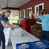 """Tully Farms Dairy in Dunstable is doing more delivery business due to the Covid-19 pandemic. Lisa Gervais of Dunstable, left, picks up her order, saying """"gotta have ice cream!"""" as Jennifer Tully (Charlie's wife) waves from the doorway at the store. (SUN/Julia Malakie)"""