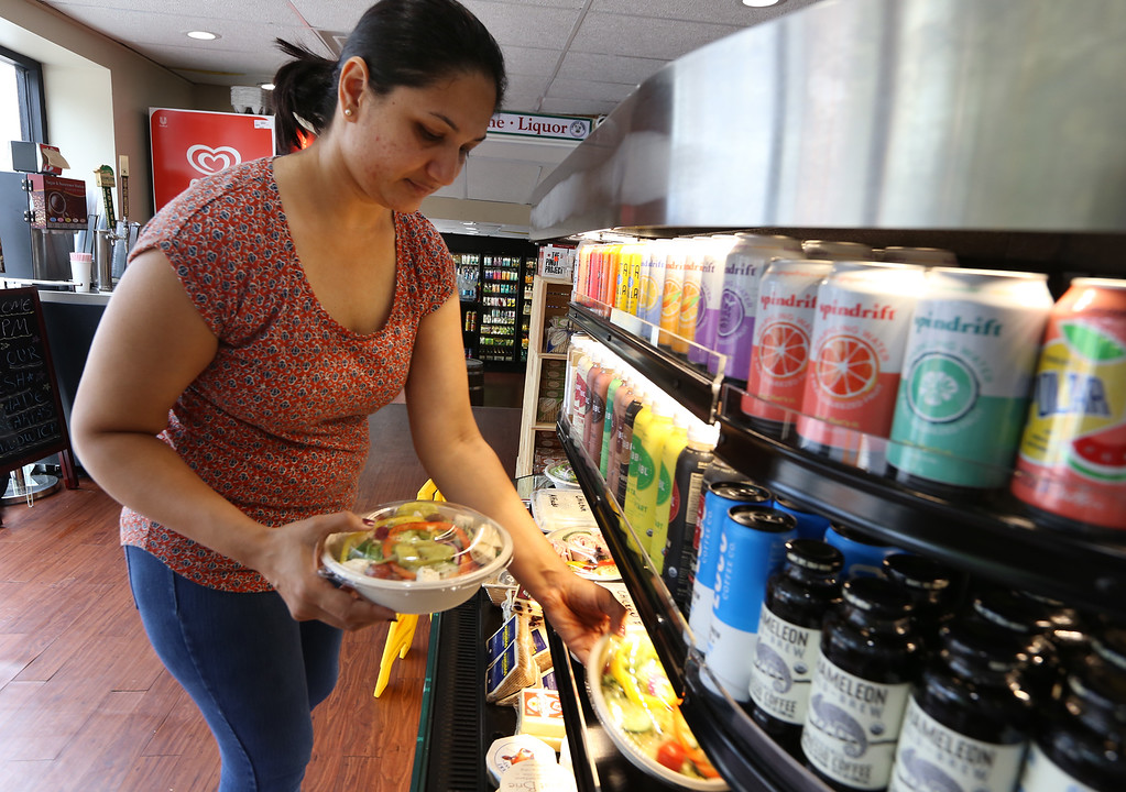 . Turnpike Market on Middlesex Turnpike in Billerica. Owner Kinnari Patel of Billerica adds some prepared meals to the shelves. (SUN/Julia Malakie)
