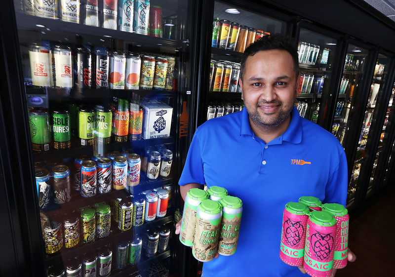 "Turnpike Market on Middlesex Turnpike in Billerica. Owner Sam Patel of Billerica, with some of the market's extensive and constantly changing selection of microbrews, ""Fear of Commitment"" by Bare Wolf Brewing in Amesbury, and ""One Hop This Time"" by Night Shift Brewing in Everett. (SUN/Julia Malakie)"