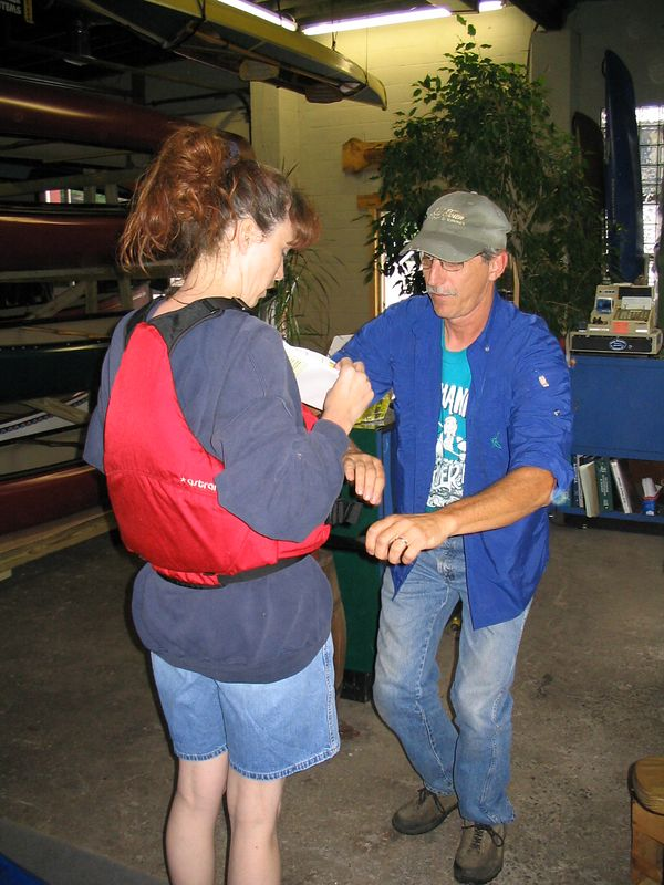 The owner helps Debbie try out a really nice PFD. Retail cost. $130. Like I said. It is a really nice one. Debbie loved it big time. She was amazed at how well it fit.