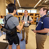 "Opening ceremony and ribbon-cutting for the UMass Lowell Fabric Discovery Center at 110 Canal. From left, Harvard PhD student Jim Soo of Cambridge demonstrating a ""soft exosuit,"" a wearable robot, Creative Materials, Inc. applications engineering manager Jon Knotts of Nashua, and Creative Materials product development engineer Brian Violette of Littleton. (SUN/Julia Malakie)"