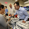 "Opening ceremony and ribbon-cutting for the UMass Lowell Fabric Discovery Center at 110 Canal. Camila Garces of Brookline, who works for materials company Saint-Gobain, gets help with setting up the LOOKs app for the ""world's first programmable backpack"" from AFFOA director of operations Steve Tran of Somerville. Each backpack pattern is different. (SUN/Julia Malakie)"
