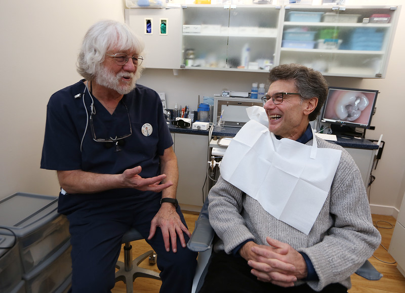 Billerica dentist Paul Feuerstein of Lowell, recently named one of the world's top 100 dentists, with his patient and neighbor, John Cipolaro of Lowell, at Billerica Dental Associates.  (SUN/Julia Malakie)