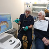 Billerica dentist Paul Feuerstein of Lowell, left, recently named one of the world's top 100 dentists, at Billerica Dental Associates, shows a 3-D image from a CEREC AC camera to patient Jerry Giuliano of Wakefield (not Giuliano's teeth).   (SUN/Julia Malakie)