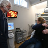 Billerica dentist Paul Feuerstein of Lowell, left, recently named one of the world's top 100 dentists, at Billerica Dental Associates, looks on as patient Jerry Giuliano of Wakefield hugs certified dental assistant Karla Brink of Chelmsford.  (SUN/Julia Malakie)