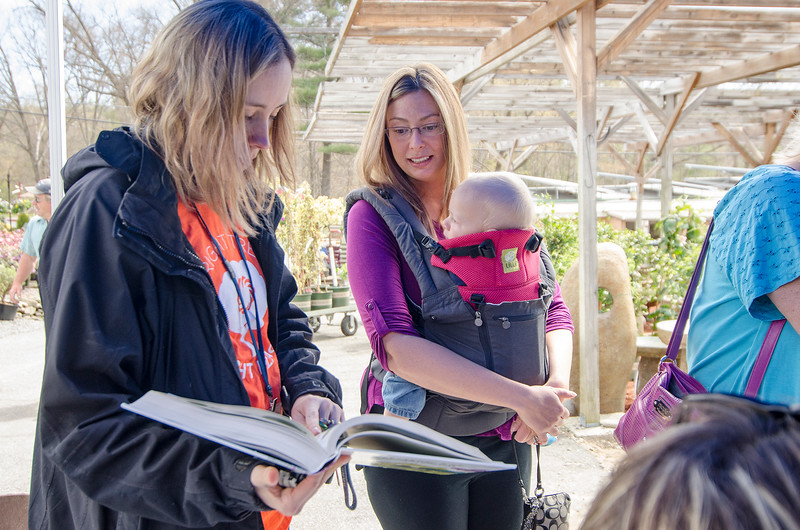 Sara Sankowich and Courtney Morse with baby Shane look through a tree booklet during the Unitil's second Annual Energy Saving Trees Community Event at Lakeview Nurseries in Lunenburg on Saturday afternoon. SENTINEL & ENTERPRISE / Ashley Green