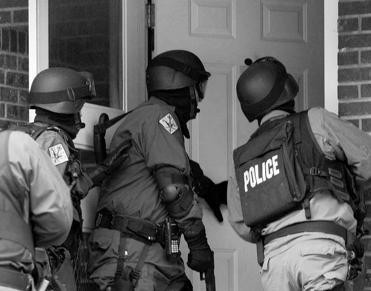 Waynesville Police officers enter a home during an early-morning drug raid on Thursday.<br /> <br /> HAYWOOD RAID NABS 'STREET-LEVEL DEALERS'