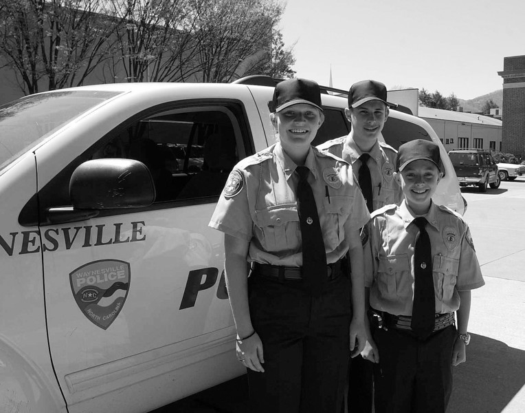 From left, Heather Hunter, Trent Parrott and Willie Jones, all 15, stand by a Waynesville Police Department vehicle last week during Haywood County's spring break for students of public schools. Heather, Trent and Willie are members of the local Explorers chapter, overseen by the police department and a program of the Boy Scouts of America. Spring break activities including getting uniforms, doing errands for the police and other outings.