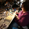 Family-owned-company, Wee Forest Folk, makes miniatures in Carlisle. Bambi Prichard of Clinton, who works in quality control, touches up figures where needed, that have been partially completed by employees at home. (SUN/Julia Malakie)