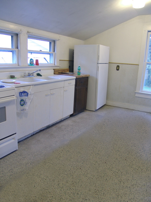 Looking into the kitchen from the dining area, towards the kitchen sink and appliance wall.<br /> Good view of linoleum, as well.