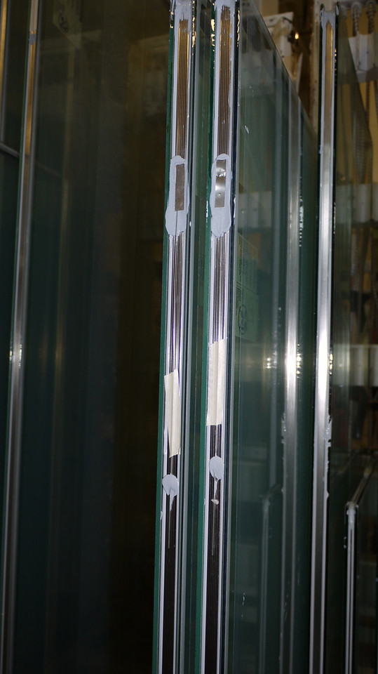 These are capillary tubes, similar to breather tubes, used to maintain the shape of the IGU when it is transported over 4500 feet of elevation difference.  For example, if it is shipped from Hood River to Calgary to be installed in a window, and then to Vancouver for sale, the seal may be compromised.  You can't put Argon Gas into an IGU with a tube.
