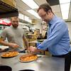 Zeda's Village Bar and Grill owner Adam Wernick teaches Working Stiff Jon Bishop how to make pizza. SENTINEL & ENTERPRISE / Ashley Green