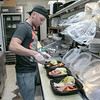The GazBar Restaurant in Leominster was still serving takeout during the coronavirus emergency on Wednesday, March 18, 2020. Head Cook Cristian Ferrin gets some takeout orders ready in the kitchen.  SENTINEL & ENTERPRISE/JOHN LOVE