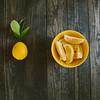 a lemon and lemon wedges on a table.