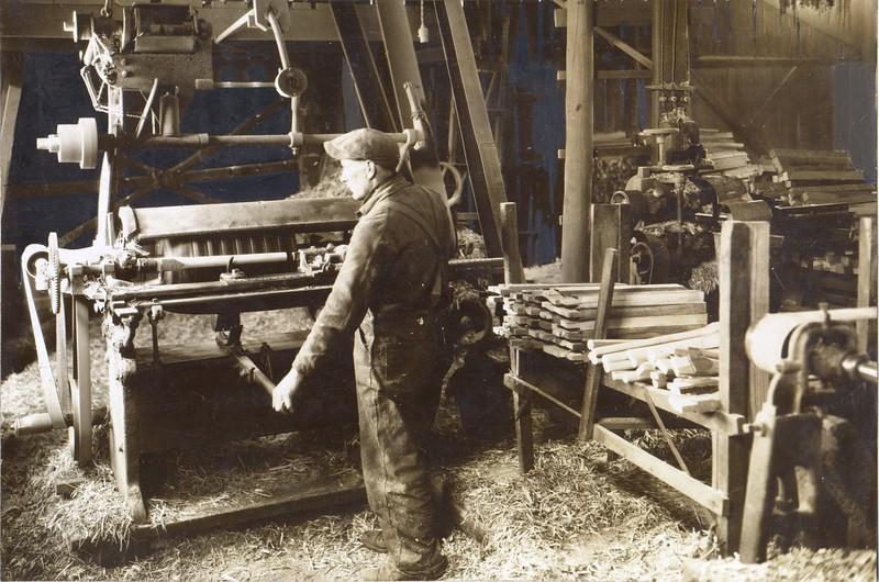 Man operating a lathe to make spokes for wagon wheels (03109)