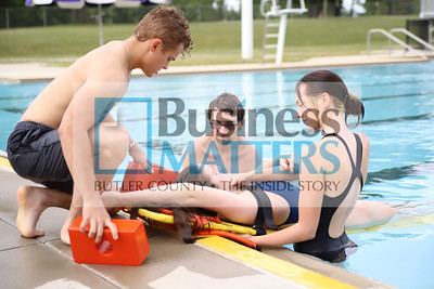 Jonah Bartholic (left), Audrey Hilliard(right) place Celia Ray on a backboard during lifeguard training with instructor Zachery Hoover (center) last Friday at the Alemeda Park pool. The pool opened to the public Wednesday. Seb Foltz/Butler Eagle 06/26/20
