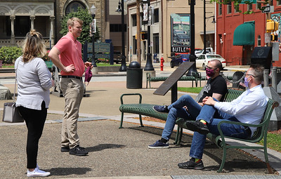 "Butler County Chamber of Commerce exectutive director Jordan Grady (center) takes advantage of sunny skies and the county's ""yellow"" designation to chat with Audrianna Bly (left), Mike Robb (right) and Chris Lunn in Diamond Park Friday. Seb Foltz/Butler Eagle"