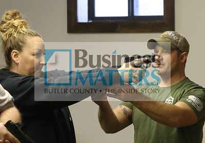 Mike Dunlap of Trigger Mike's Firearms Training helps April Kuhns of Butler with her hand position during a gun safety class at the Buffalo Sportsman Club. Seb Foltz/Butler Eagle 01/09/20