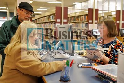 Cranberry Library circulation clerk Barbara Rosenbaum signs out books for Linda and Roger Cwynar of Cranberry. Seb Foltz/Butler Eagle