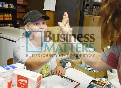 "Harold Aughton/Butler Eagle: Volunteer Christina Pistorius high fives a new client after registering her to access the Petroleum Food Cupboard, Friday, July 17, 2020.  Cars lineup outside the Petroleum Food Cupboard, Friday, July 17, 2020. The Cupboard provides food for Northeastern Butler County including Fairview Borough, Parker, Allegheny and Donegal townships. However according to Rev. John Pistorius, pastor of the Christ Family Church in Chicora, ""We don't turn anybody away.""  The Cupboard opens from 9 am – Noon or until food runs out every third Friday of the month. If you are in need of assistance or want to donate to the Cupboard, call 724.679. 6062. The Cupboard is located in the old United Methodist Church in Fairview, 120 Chestnut Street, Petrolia."