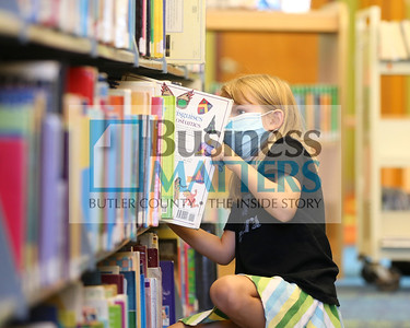 Wearing her mask, soon-to-be second grader Cora Monhemius, 7, of Cranberry browses for books at the Cranberry Public Library Tuesday. Seb Foltz/Butler Eagle