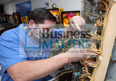 Tokens Arcade owner Chris Henry inspects an electrical component of one of the arcade's pinball machines. Seb Foltz/Butler Eagle 01/29/21