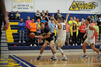 Knoch #15 Jared Schrecengost passes the ball around Freeport #23 Andrew Speer during a game at Freeport Gym on Tuesday January 14, 2020 (Jason Swanson photo)