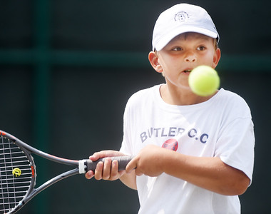 Tripp Santora prepares to return a serve during the Junior Inter-Club Mixed Doubles match at the Butler Country Club Thursday morning. Harold Aughton/Butler Eagle.