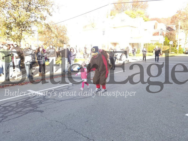 Jim Smith photoA young participant gets a helping hand from the race mascot to finish Saturday's one-mile kids run at the 38th Annual Butler YMCA Turkey Trot in Butler. The event, which featured a 5K, attracted about 350 runners despite freezing temperatures. 3 col pic