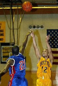 Butte College's #12 Brian Smith takes a shot over Siskiyous College's #21 DeMario Ballard with about 7:14 remaning in the first half of thier basketball game Wednesday. - halley photo 2/1/06