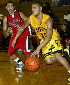 Butte College's #12 Brian Smith drives toward the basket around Foothill College's #3 Sam Obando with about 4:03 to go during the first half of thier basketball game Saturday. - halley photo 1/7/05