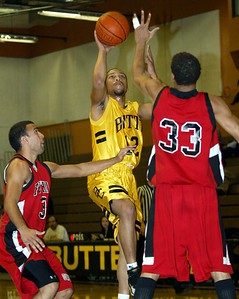 Butte College's #12 Brian Smith puts up a shot over Foothill College's #3 Sam Obando (left) and #33 Khori Sandifer (right) with about 16:30 to go during the first half of thier basketball game Saturday. - halley photo 1/7/05