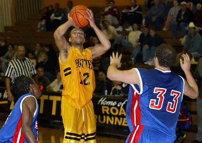 Butte College's #12 Brian Smith takes a shot over Siskiyous College's #15 Terrell Burgess (left) and #33 Chris Rodriguez with about 0:10 remaning in the first half of thier basketball game Wednesday. - halley photo 2/1/06