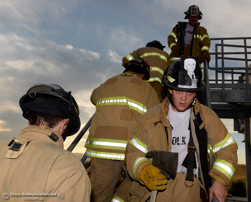 . At right, Brandon Olk along with members of the 68th Butte College Fire Academy carry hoses and tools as they climb 110 floors of stairs to replicate the flights of stairs that fallen firefighters took on Sept. 11, 2001. Each cadet researched a fallen firefighter and wears a photo of that firefighter on their helmet during the memorial tribute Wed. Sept. 13, 2017.  (Bill Husa -- Enterprise-Record)