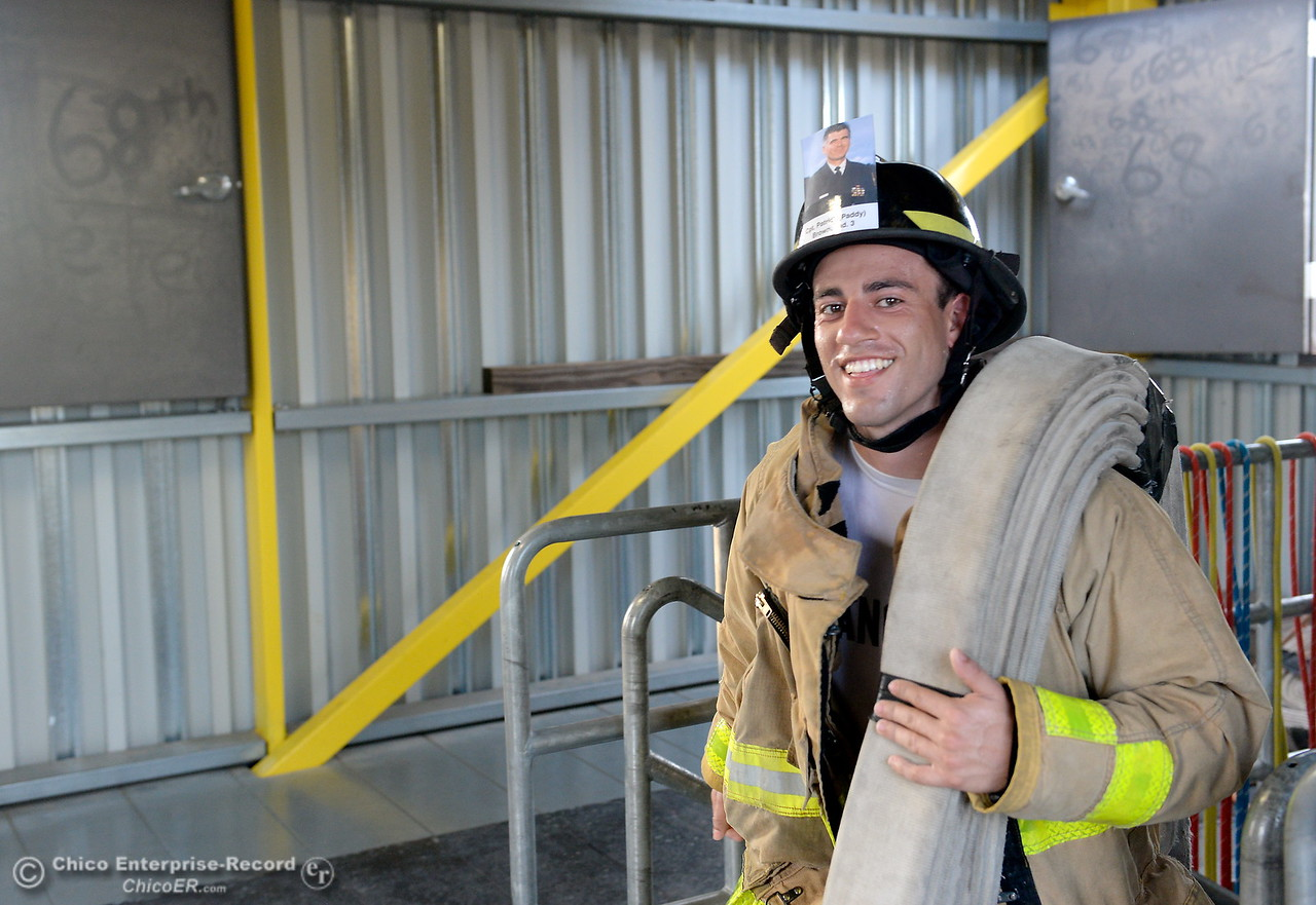 Xavier Sanchez manages to smile as he and members of the 68th Butte College Fire Academy carry hoses and tools as they climb 110 floors of stairs to replicate the flights of stairs that fallen firefighters took on Sept. 11, 2001. Each cadet researched a fallen firefighter and wears a photo of that firefighter on their helmet during the memorial tribute Wed. Sept. 13, 2017.  (Bill Husa -- Enterprise-Record)