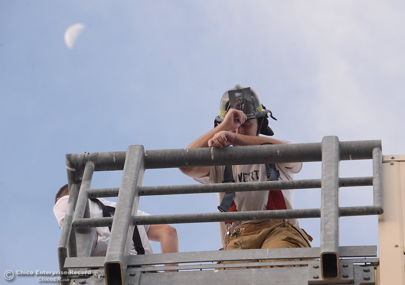Joshua Vert catches his breath on the top of the staris as members of the 68th Butte College Fire Academy finish carrying hoses and tools while they climbed 110 floors of stairs to replicate the flights of stairs that fallen firefighters took on Sept. 11, 2001. Each cadet researched a fallen firefighter and wears a photo of that firefighter on their helmet during the memorial tribute Wed. Sept. 13, 2017.  (Bill Husa -- Enterprise-Record)
