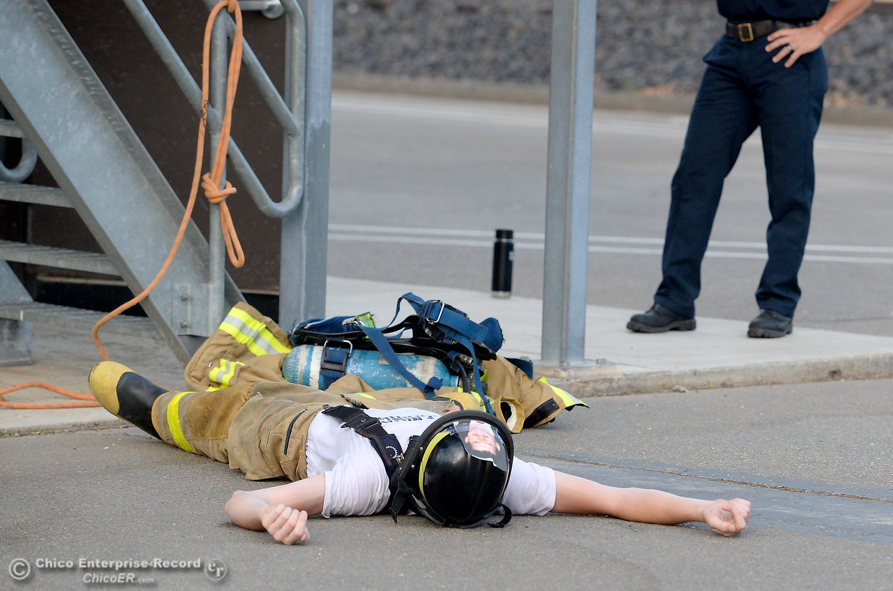 An exhausted cadet takes a short breather as members of the 68th Butte College Fire Academy finish carrying hoses and tools while they climbed 110 floors of stairs to replicate the flights of stairs that fallen firefighters took on Sept. 11, 2001. Each cadet researched a fallen firefighter and wears a photo of that firefighter on their helmet during the memorial tribute Wed. Sept. 13, 2017.  (Bill Husa -- Enterprise-Record)