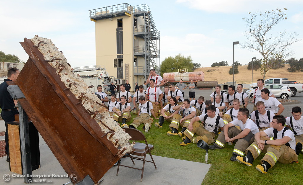 . Members of the 68th Butte College Fire Academy listen to Captain Mike Murphy as he tolls the bell in honor of fallen firefighters from the attacks on Sept. 11, 2001. Each cadet researched a fallen firefighter and wore a photo of that firefighter on their helmet during the memorial tribute Wed. Sept. 13, 2017.  (Bill Husa -- Enterprise-Record)
