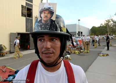 Michael Chavarria tells the story of Billy McGinn, a firefighter with the 18th squadron of Search & Rescue who was among the first on scene as members of the 68th Butte College Fire Academy carry hoses and tools as they climb 110 floors of stairs to replicate the flights of stairs that fallen firefighters took on Sept. 11, 2001. Each cadet researched a fallen firefighter and wears a photo of that firefighter on their helmet during the memorial tribute Wed. Sept. 13, 2017.  (Bill Husa -- Enterprise-Record)