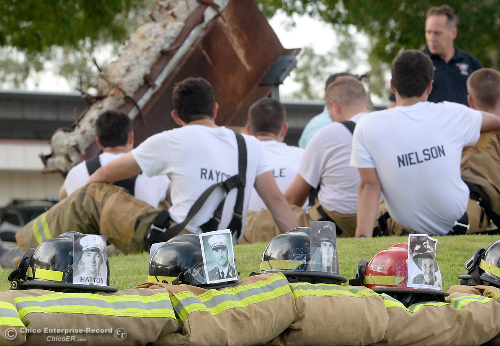 . Members of the 68th Butte College Fire Academy rest and listen to speakers after they climbed 110 floors of stairs to replicate the flights of stairs that fallen firefighters took on Sept. 11, 2001. Each cadet researched a fallen firefighter and wears a photo of that firefighter on their helmet during the memorial tribute Wed. Sept. 13, 2017.  (Bill Husa -- Enterprise-Record)