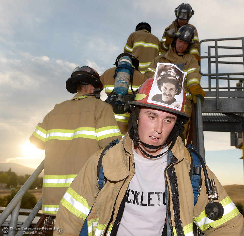 Joseph Shackelton, front right, and members of the 68th Butte College Fire Academy carry hoses and tools as they climb 110 floors of stairs to replicate the flights of stairs that fallen firefighters took on Sept. 11, 2001. Each cadet researched a fallen firefighter and wears a photo of that firefighter on their helmet during the memorial tribute Wed. Sept. 13, 2017.  (Bill Husa -- Enterprise-Record)