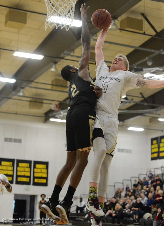 . Butte College\'s Logan Rooney goes up for a shot over Marin\'s Derek Morgan Tuesday November 28, 2017 at Butte College in Butte Valley, California. (Emily Bertolino -- Enterprise-Record)