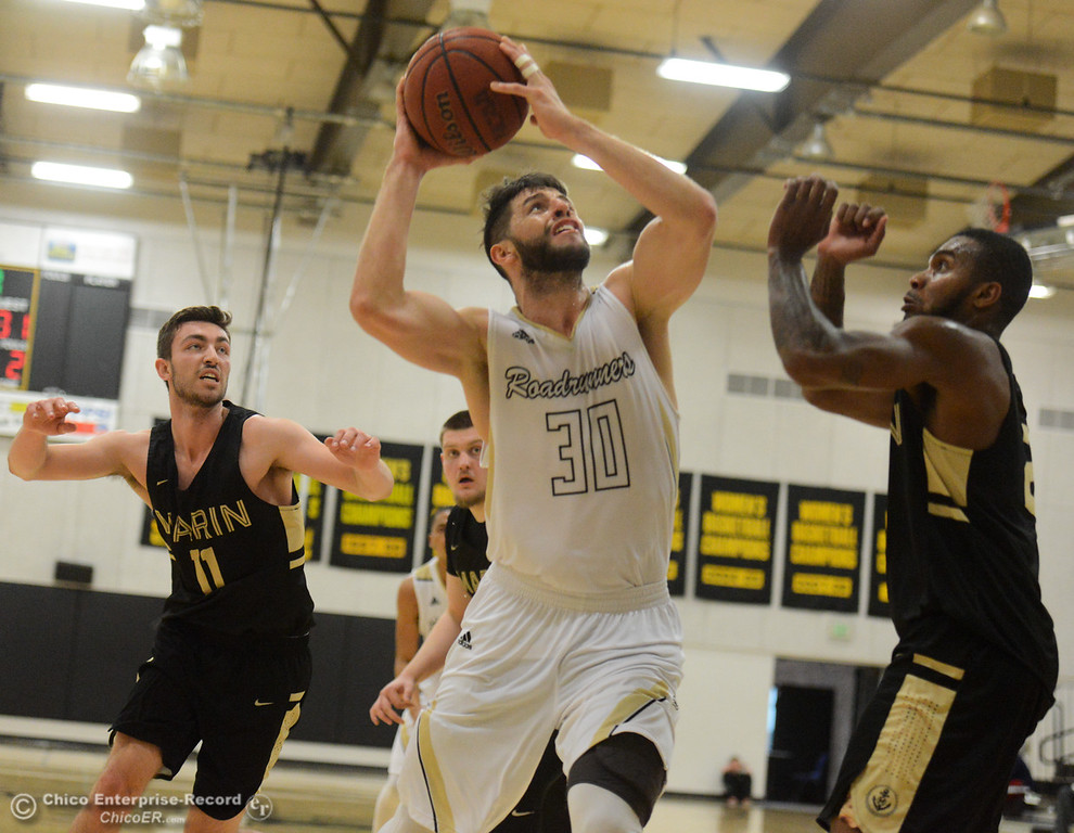 . Butte College\'s Carlos Costa goes up for a shot over Marin\'s Derek Morgan Tuesday November 28, 2017 at Butte College in Butte Valley, California. (Emily Bertolino -- Enterprise-Record)